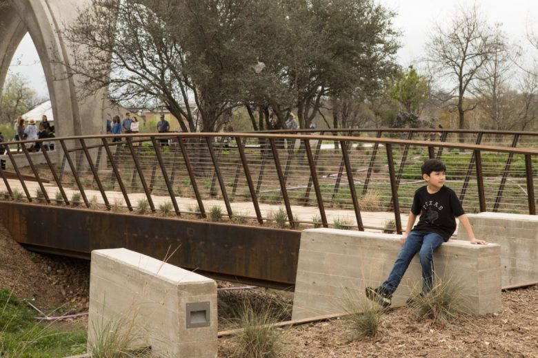 A young boy sits next to the bridge at Confluence Park which crosses the so-called embayment, where underground rainwater harvesting structures are buried.