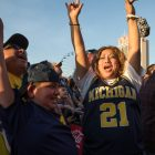 (From left) Andres Flores, Angel Martinez, and Erma Martinez scream in excitement after Michigan University beats Chicago Loyola University during the 2018 NCAA Final Four.