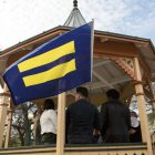 LGBTQIA leaders hold an equality flag to protest a ruling made in the case of Kenne McFadden.