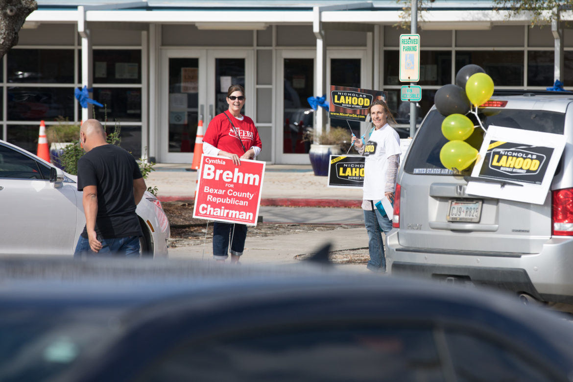 Electioneers at the Harmony Hills Elementary School polling location approach a voter as he approaches the site.
