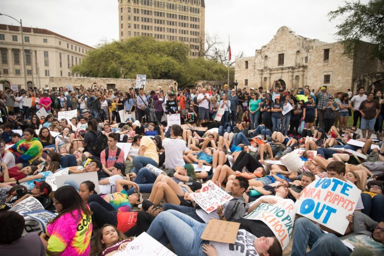 Students participate in a 'die in' in front of the Alamo.