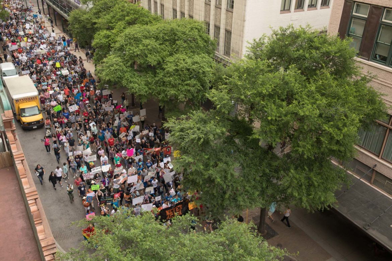 Marchers along Houston Street head East towards the Alamo.