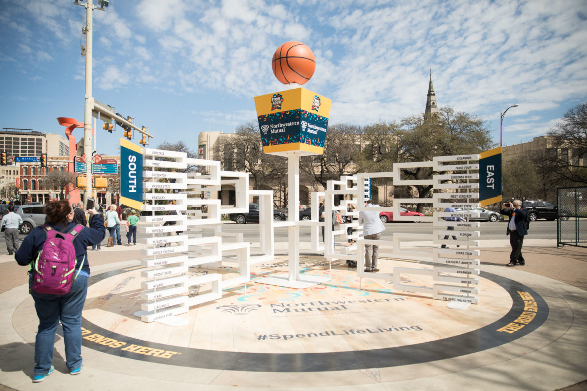 A large sized bracket of the final four contenders sits at the corner of Alamo and Market Streets.