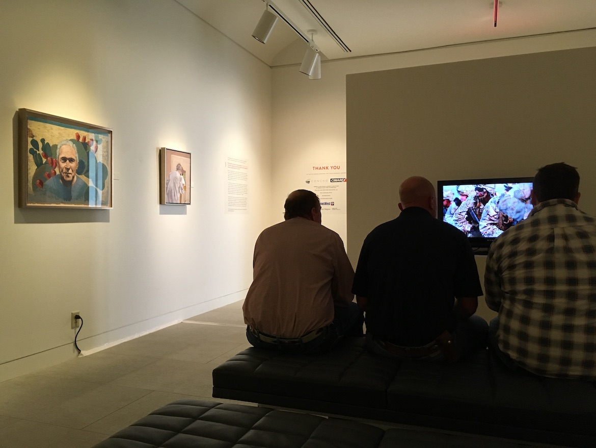 """Three military veterans view the introductory video to George W. Bush's """"Portraits of Courage"""" exhibition at the Museum of the Southwest in Midland, Texas. A portrait of Bush by painter Jim Woodson hangs at left."""