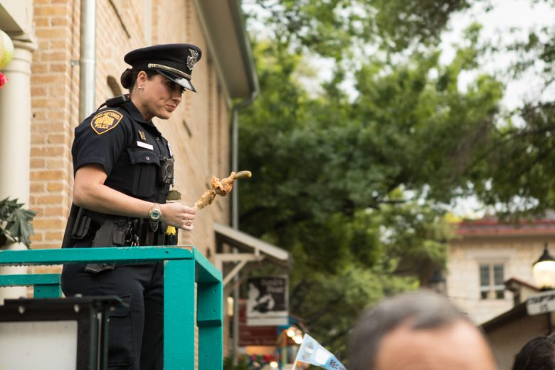 A police officer eats chicken on a stick as she watches over crowds.