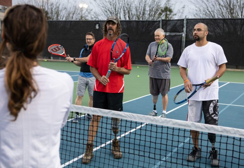 Members of the Full Metal Racquets team listen to their coach during practice.