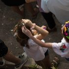 Parade-goers crack cascarones on each other's heads.