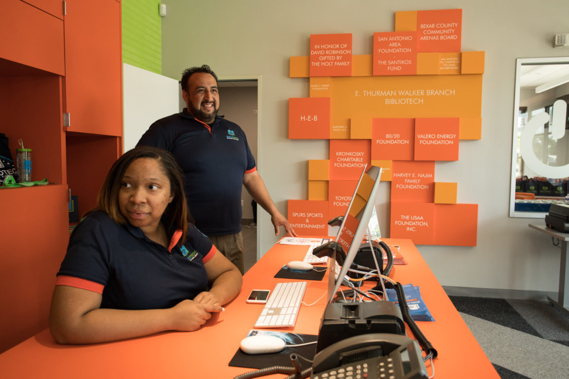 (From left) Technical assistants Angela Littlefield and Raul Martinez sit at the welcome desk in Bexar County's third full-service BiblioTech branch on the East Side.