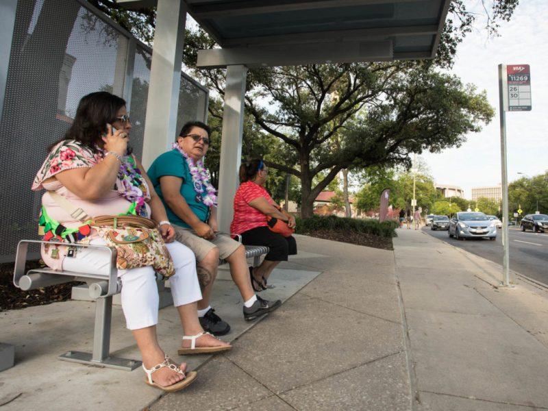 (From left) Debra Mora, Gloria Longoria, and Laura Villegas wait for their bus after attending Fiesta Fiesta at Hemisfair.