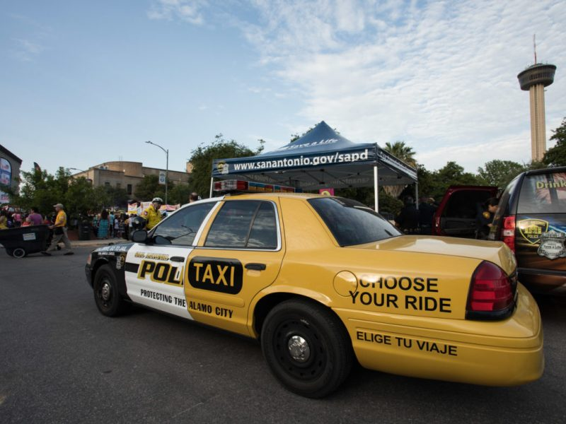 A combination of a police car and a taxi warns fiesta-goers not to drink and drive.