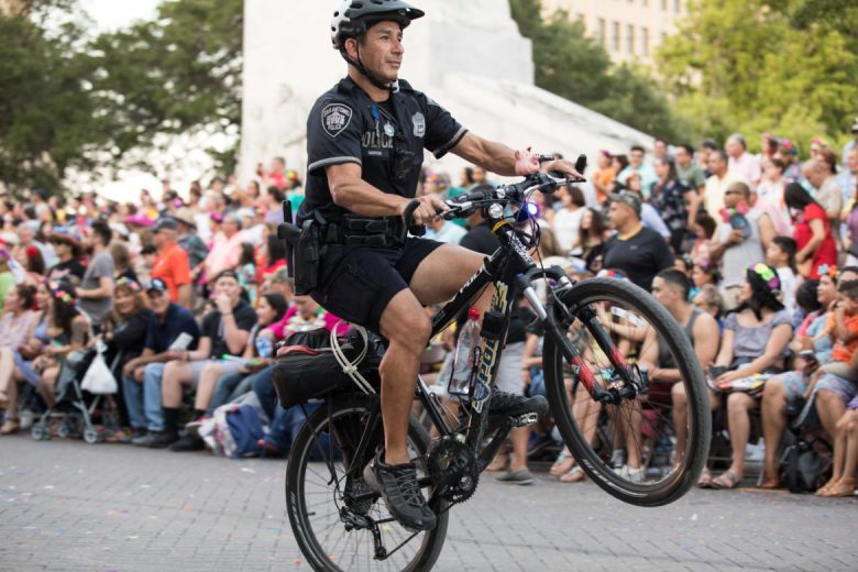 A police officer performs a wheelie before the parade officially begins.