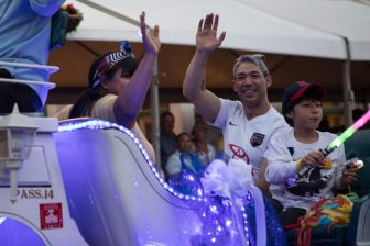 (From left) Erika Prosper, Mayor Ron Nirenberg, and their son Jonah ride on a float down Alamo Street.
