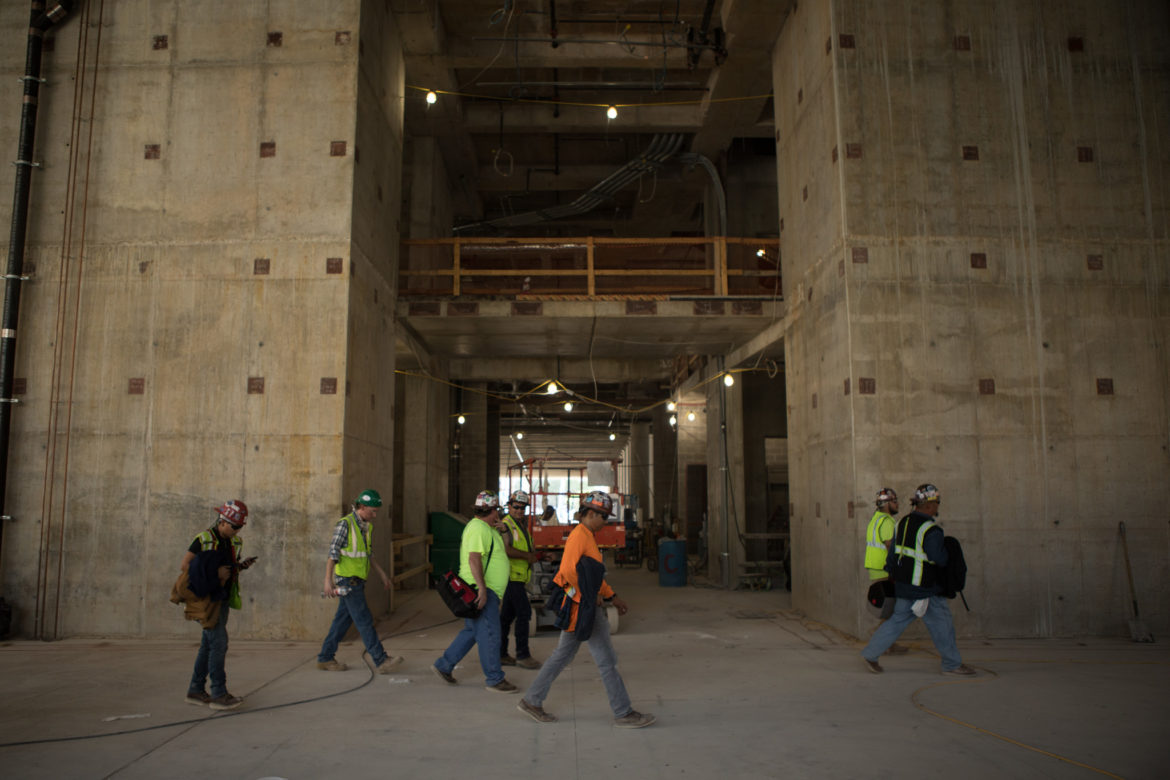 Construction workers walk through the lobby of the Frost Tower construction site.