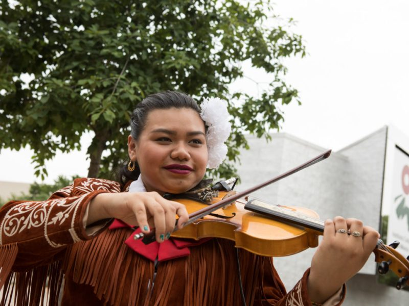 Natalia Alejandra Ramírez Juárez, of Trio Nueva Herencia, practices before performing at the ¡Viva Hemisfair! Friday Kick-Off at Yanaguana Garden.