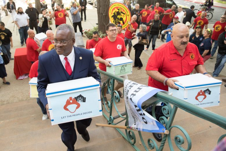 San Antonio Professional Firefighter Union President Chris Steele delivers petitions to City Hall.
