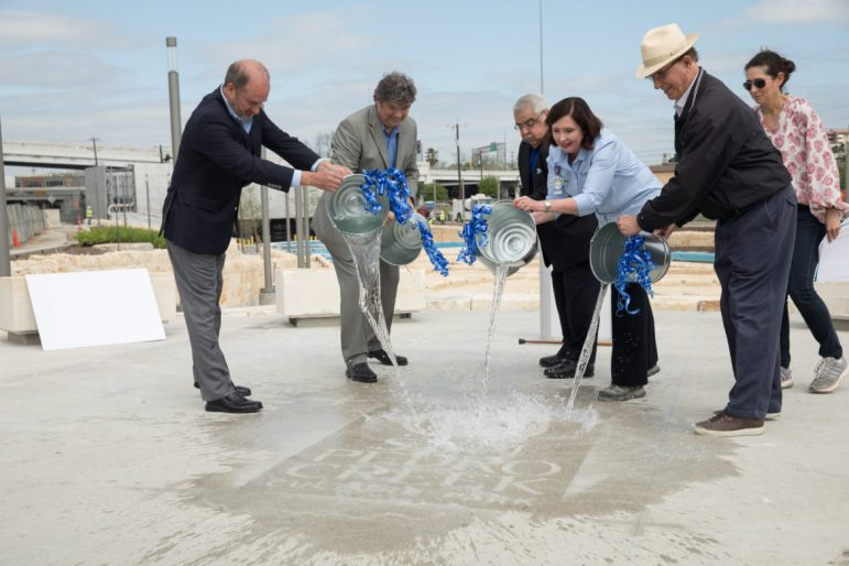San Antonio River Authority personell along with County officials pour water unveiling the new San Pedro Creek Culture Park logo.