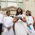 Jains perform a song in front of the Municipal Plaza Building.