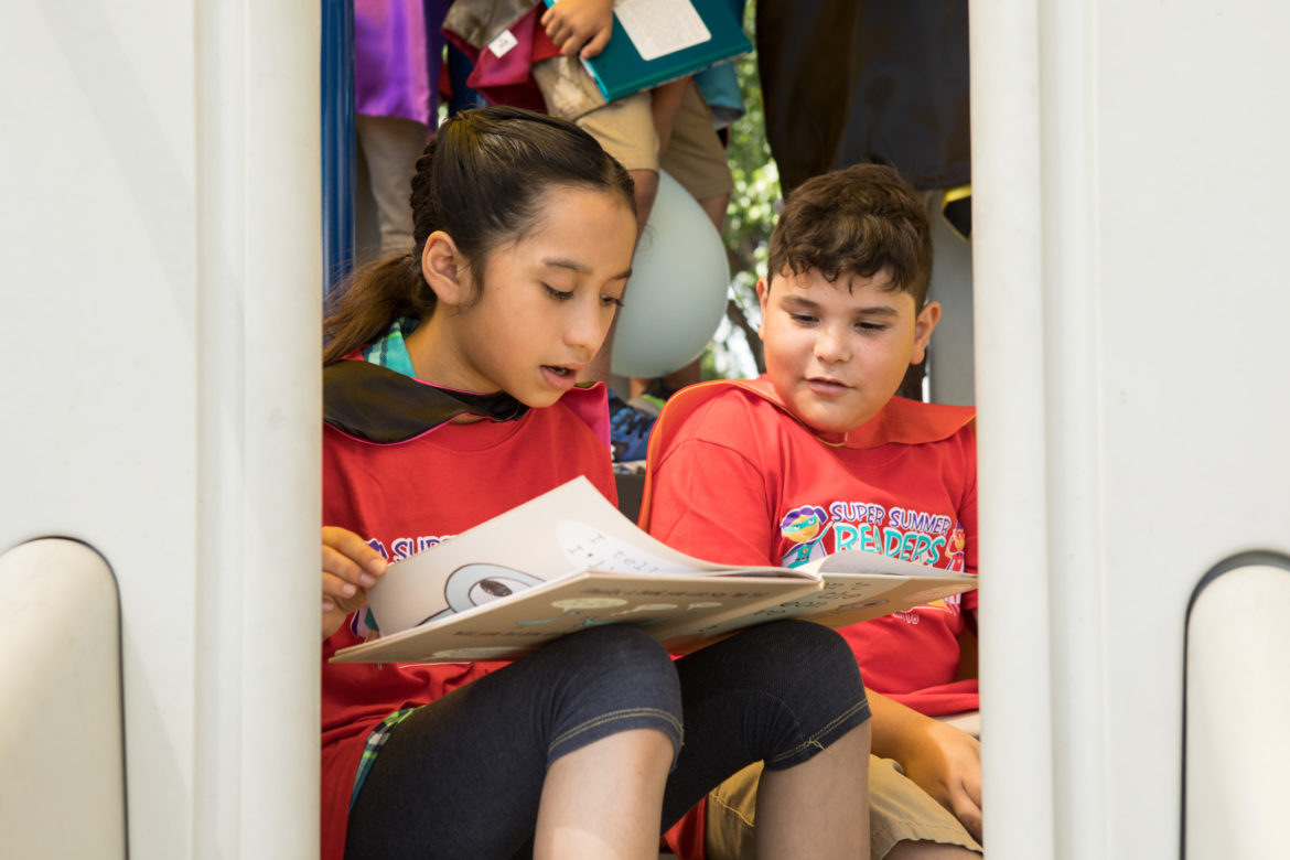SAISD Harlandale students read their first books in the Super Summer Readers Program on Mays Boys & Girls Club playground.