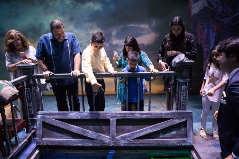 Anne Frank Inspire Academy winners admire the trap door of the set.
