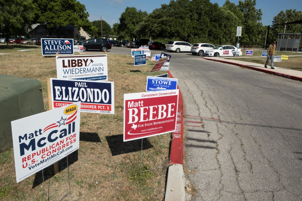 Campaign signs are displayed at the entrance to Lions Field.