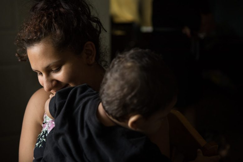 Monica Lara lifts her son Jordan into her lap.