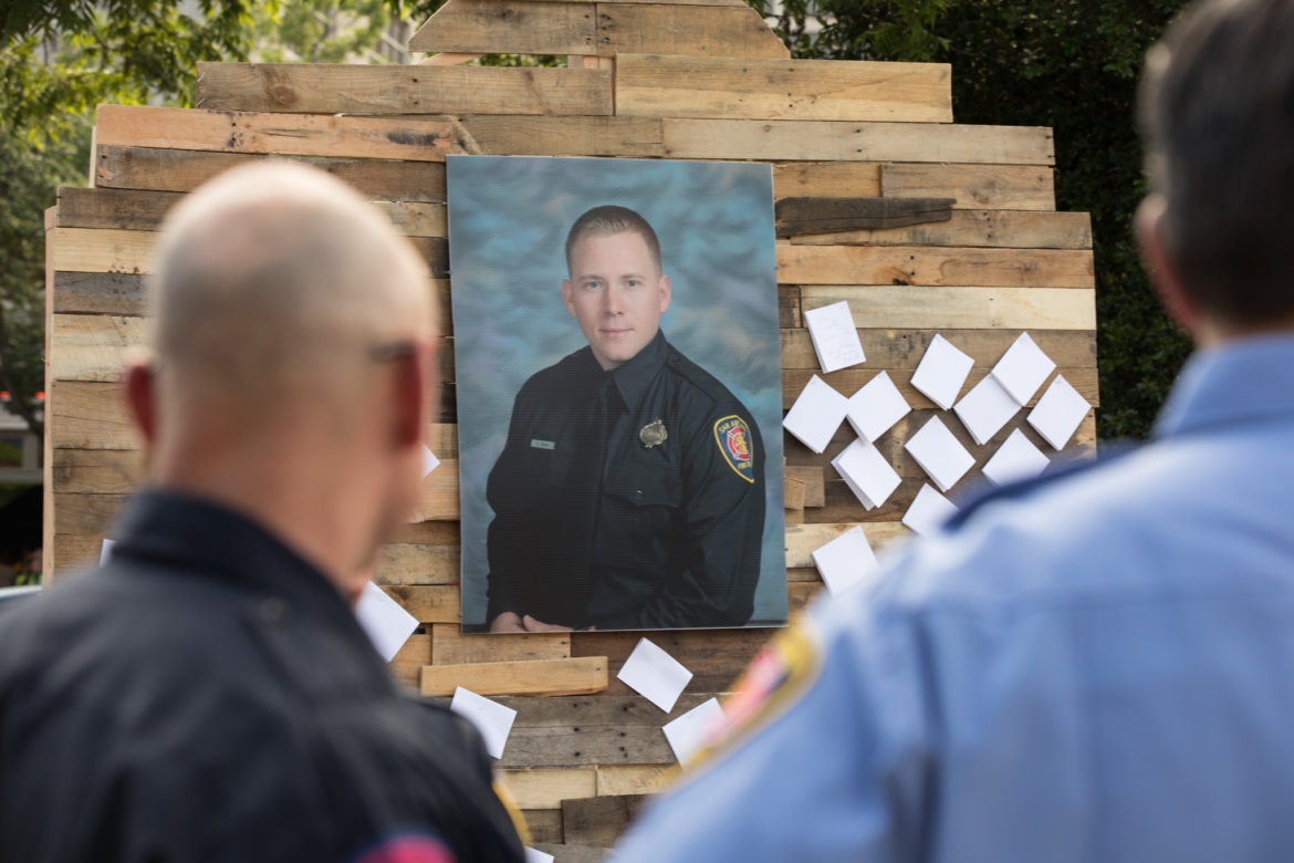 The crowd writes notes to Scott Deem and places them next to his photograph in Alamo Plaza.