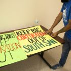 """Protest signs are displayed on a table outside of the board room, reading """"Keep Big Corporation out of South San."""""""