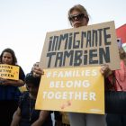"""The crowd holds signs in support of the """"Families Belong Together"""" movement."""