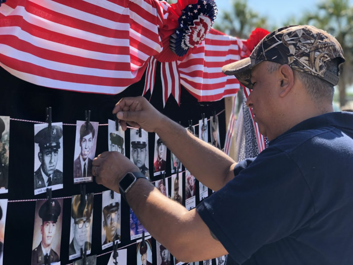 A family member places a photo of Corporal Enrique Bernal at the Edgewood Veterans Vietnam Memorial