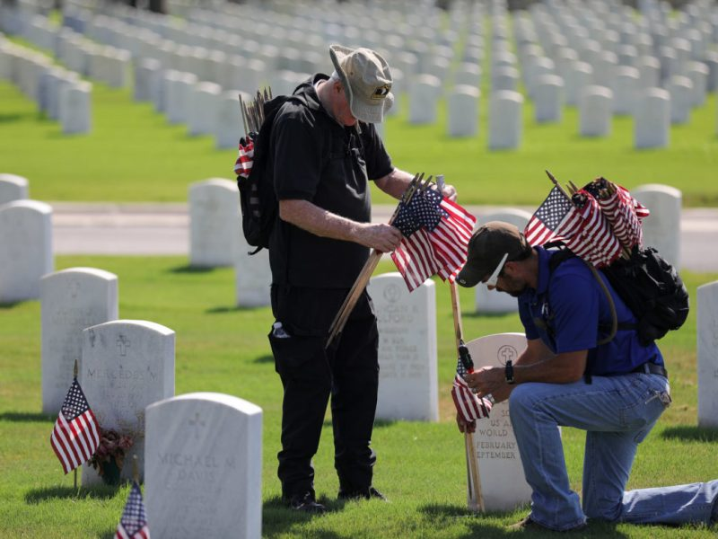 Veterans from the 101st Airborne Division Nigel Benchoff (right) and Jack Branson place flags at the headstones of deceased service men and women at Fort Sam National Cemetery.