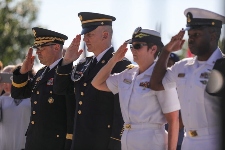 Members representing each branch of the military salute the colors as they are presented.