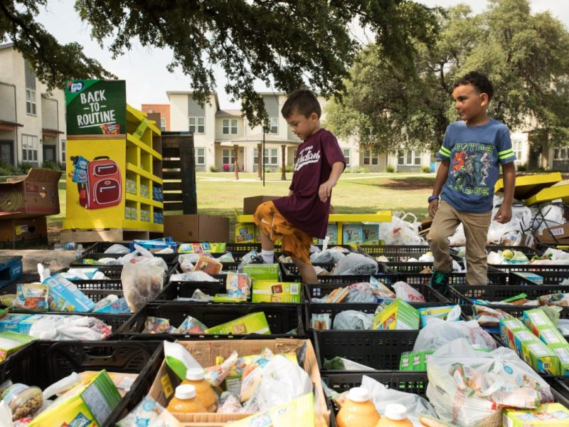 (From left) Rocky, 6, and Landon, 6, carefully walk through the crates of food.