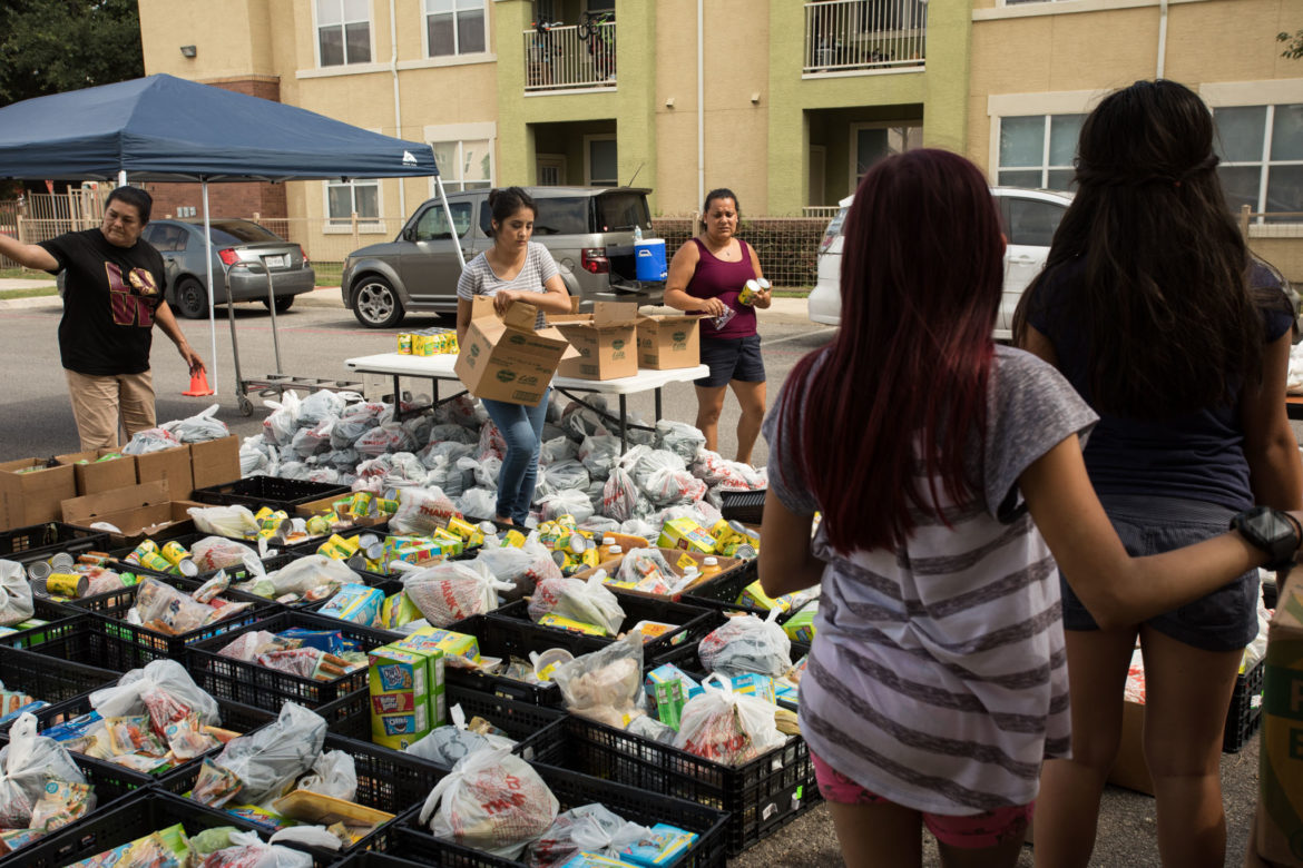 Volunteers empty cans of pears into individual crates.
