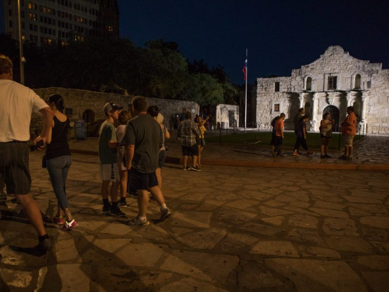 Tourists walk by the Alamo just after dusk.