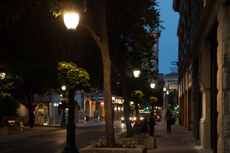 Street lamps along Houston Street brighten the way for pedestrians.