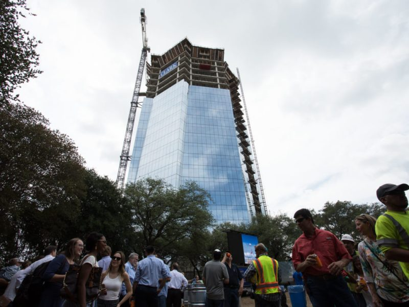 Hundreds of construction workers gather near Frost Tower for a steak dinner.