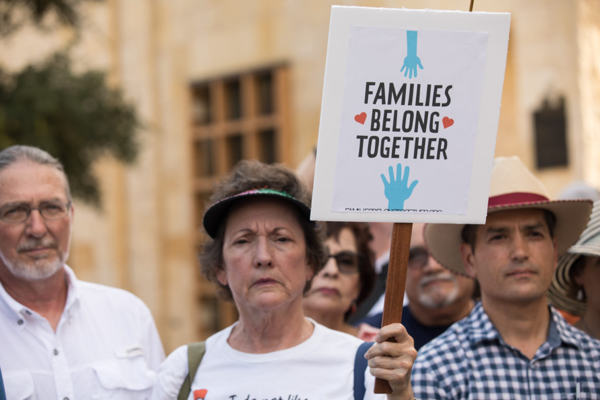 """A woman holds up a sign that reads: """"families belong together."""""""