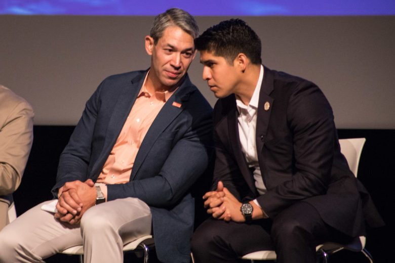 Mayor Ron Nirenberg (left) whispers to Councilman Rey Saldaña (D4) on stage.