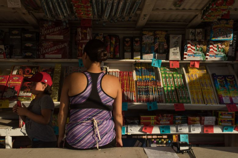 (From left) Catalina, 9, and Jessica Camacho organize the fireworks on the shelves.