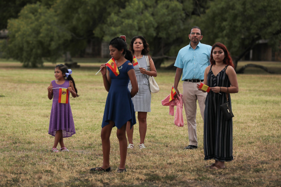 The Ortiz family watch as Spanish royalty walks through the grounds of Mission San José.
