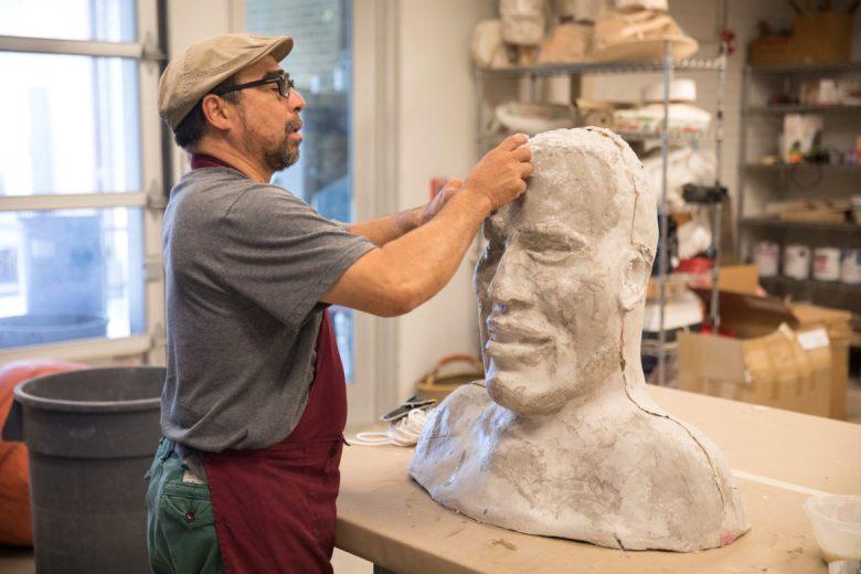 Michael Tejeda adds paper mâché to a sculpture.