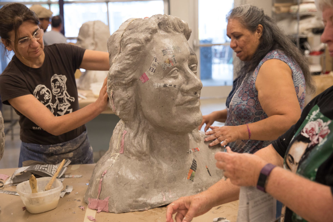 A group of artists work together to form a large paper mâché head.