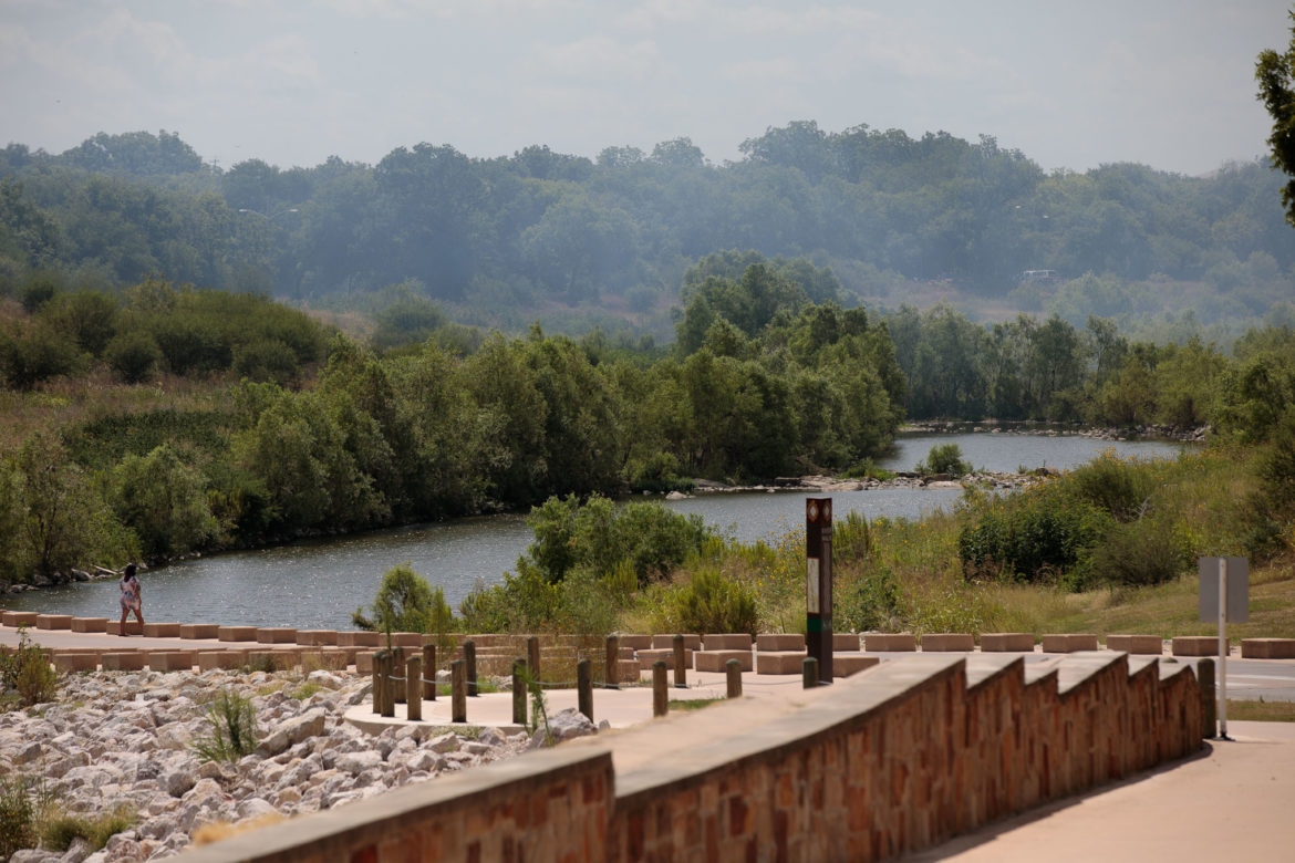 A pedestrian stands near the Acequia Bridge along the mission reach while white clouds of smoke fill the distant air.