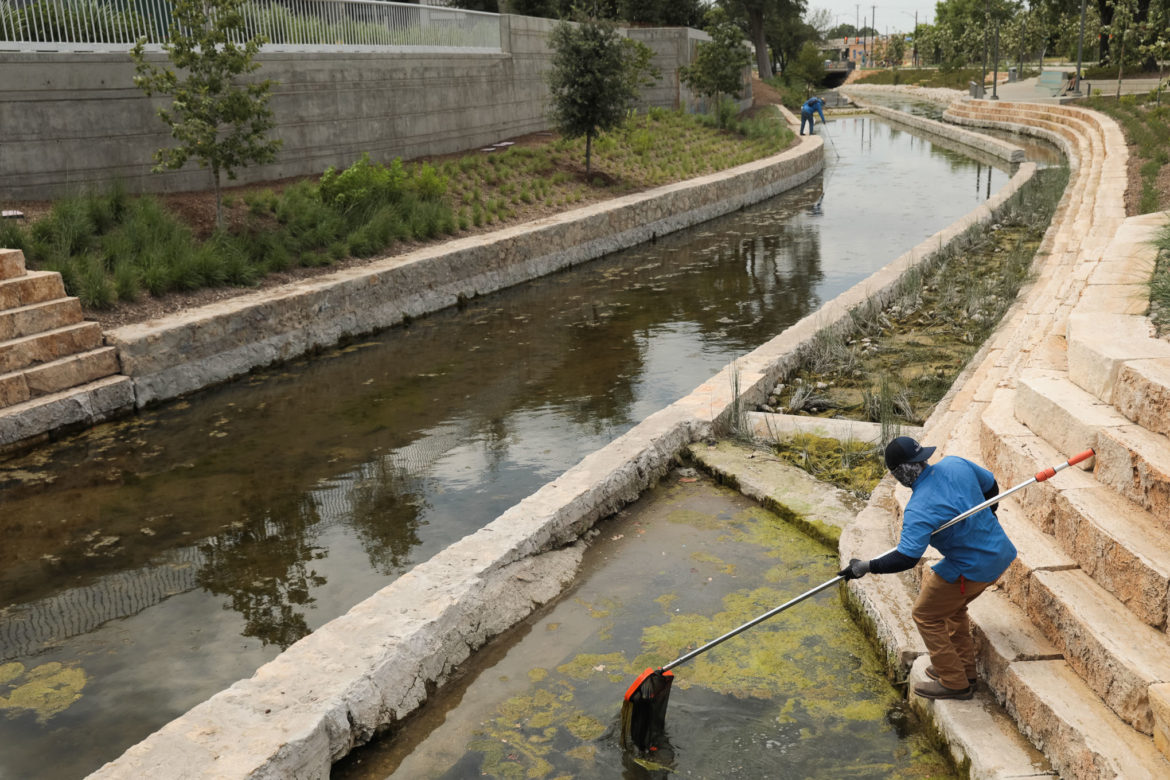 San Antonio River Authority employees work to clean litter and debris from San Pedro Creek Culture Park.