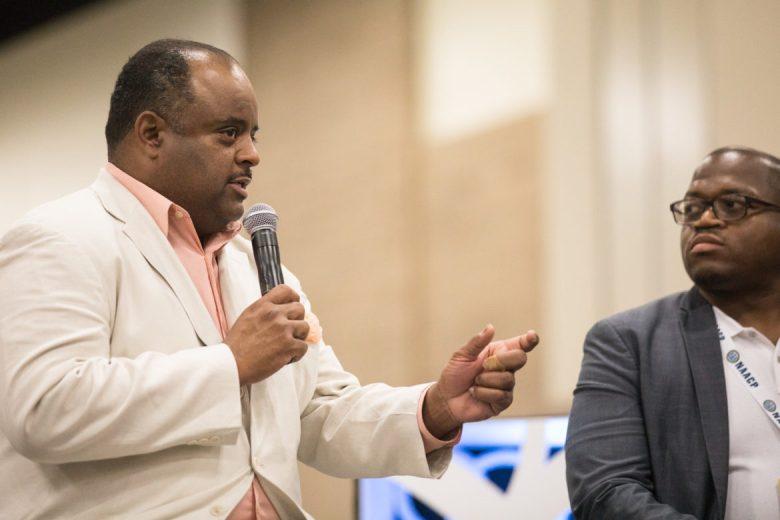 Journalist Roland Martin moderates the panel.