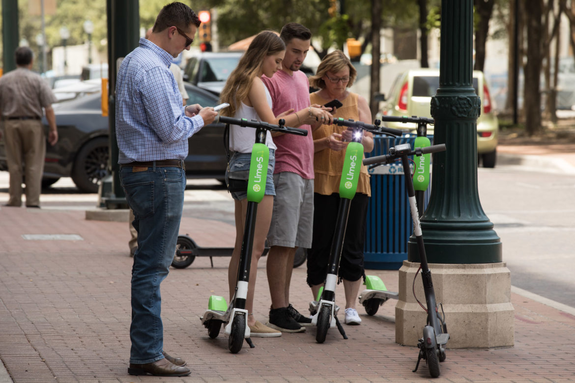 A group of people use their phones to connect with both Lime and Bird scooters in front of the Rand Building.