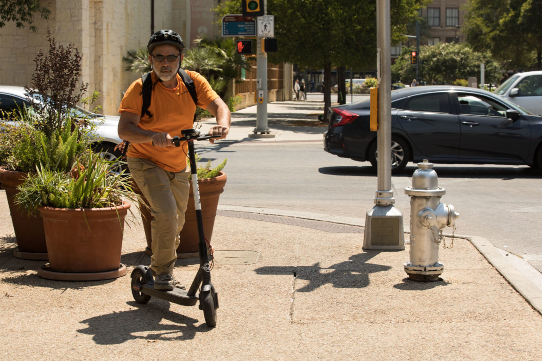Rivard Report Director Robert Rivard rides a Bird scooter on the corner of Nueva Street and South Flores Street.