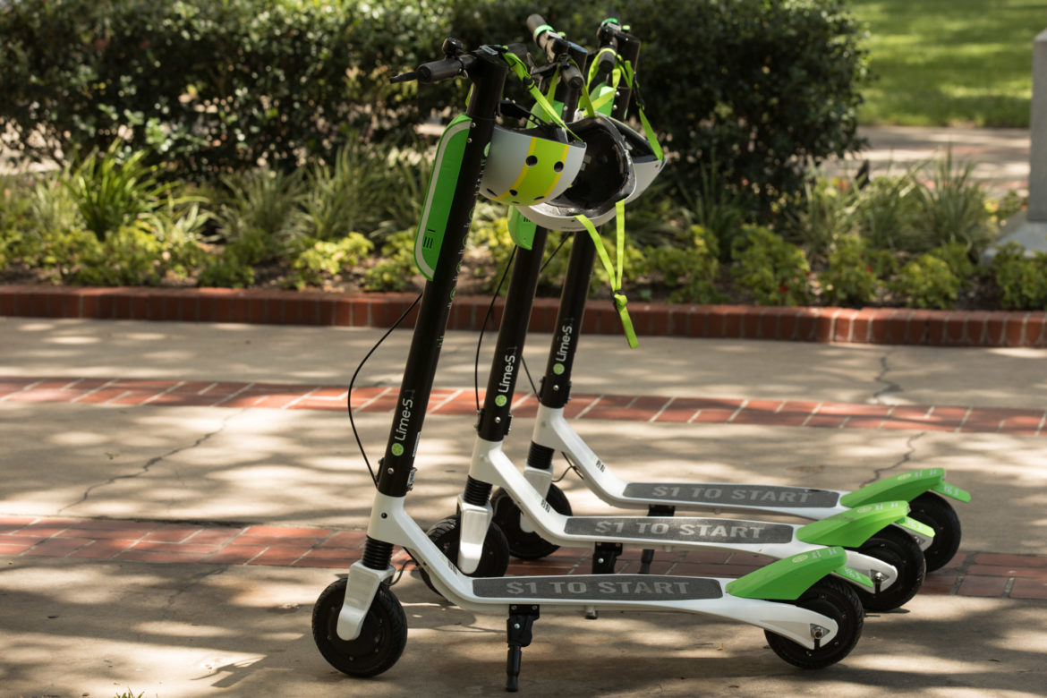 Lime-S electric scooters are lined up next to City Hall.