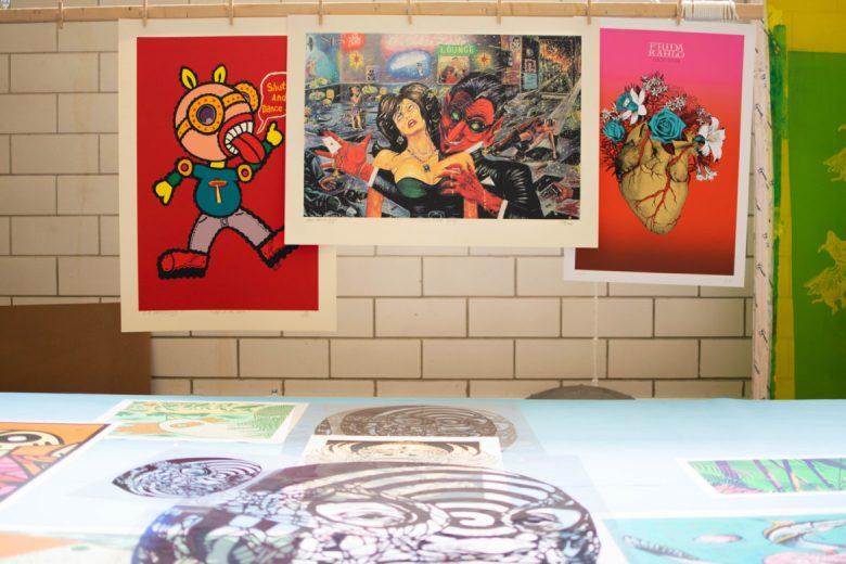 Prints hang up on display at La Printería.