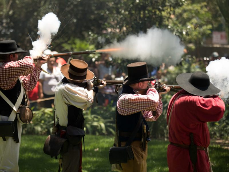 Muskets spark and smoke as they fire blanks behind the Alamo during a firing demonstration.
